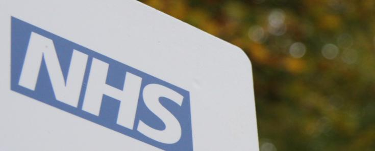NHS logo on a sign with vegetation in the background (C) EKN